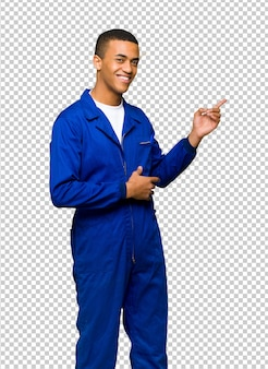 Junger afroamerikanischer arbeitskraftmann, der finger auf die seite in seitlicher position zeigt