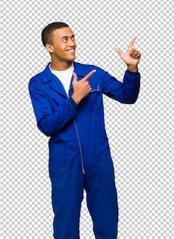 Junger afroamerikanischer arbeitskraftmann, der mit dem zeigefinger zeigt und oben schaut