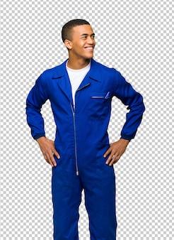 Junger afroamerikanischer arbeitskraftmann, der mit den armen an der hüfte und am lachen aufwirft