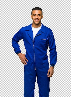 Junger afroamerikanischer arbeitskraftmann, der mit den armen an der hüfte und am lächeln aufwirft