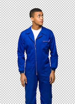 Junger afroamerikanischer arbeitskraftmann, der oben mit ernstem gesicht schaut
