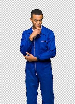 Junger afroamerikanischer arbeitskraftmann, der unten mit der hand auf dem kinn schaut