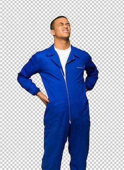 Junger afroamerikanischer arbeitskraftmann, der unter rückenschmerzen leidet, weil er sich bemüht hat