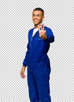 Junger afroamerikanischer arbeitskraftmann glücklich und drei mit den fingern zählen