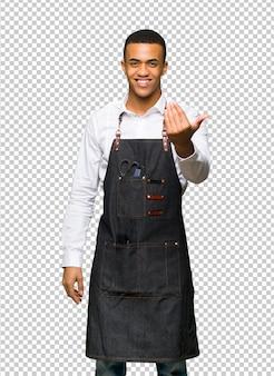 Junger afroamerikanischer friseurmann, der einlädt, mit der hand zu kommen. glücklich, dass du gekommen bist