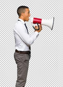Junger afroamerikanischer geschäftsmann, der durch ein megaphon schreit, um etwas in seitlicher position anzukündigen