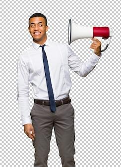 Junger afroamerikanischer geschäftsmann, der ein megaphon nimmt, das viele geräusche macht