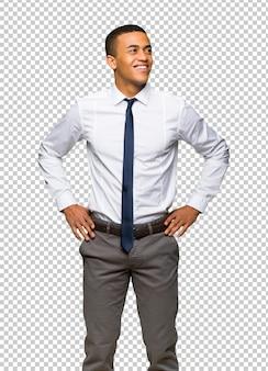Junger afroamerikanischer geschäftsmann, der mit den armen an der hüfte und am lachen aufwirft