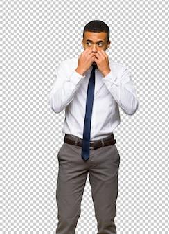 Junger afroamerikanischer geschäftsmann ist ein bisschen nervös und erschrocken, die hände zum mund zu setzen