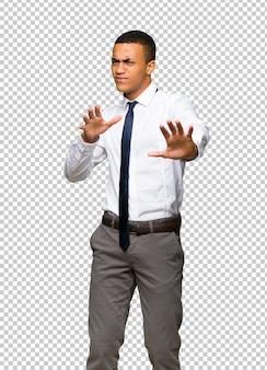 Junger afroamerikanischer geschäftsmann ist ein bisschen nervös und erschrocken, die hände zur front ausdehnend
