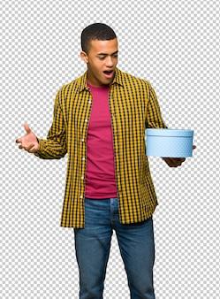 Junger afroamerikanischer mann, der geschenkbox in den händen hält