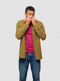 Junger afroamerikanischer mann ist ein bisschen nervös und erschrocken, die hände zum mund zu setzen