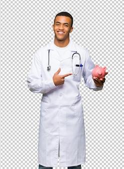 Junger afroamerikanischer manndoktor, der ein piggybank hält