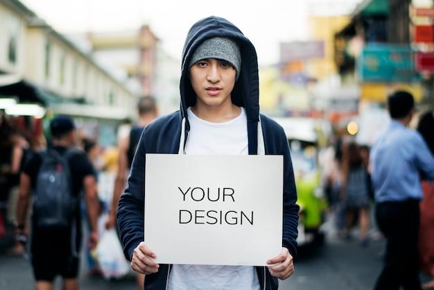 Junger asiatischer mann, der draußen leeres plakat hält