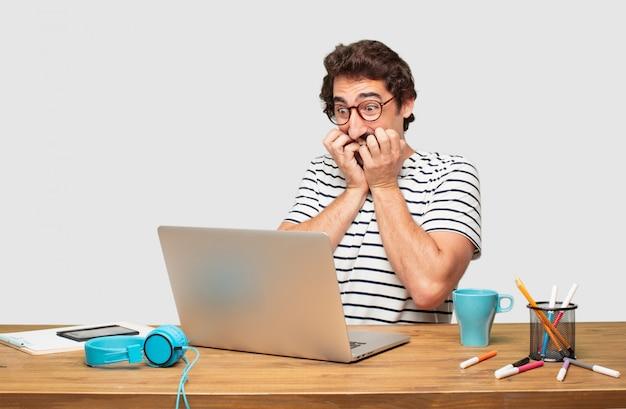 Junger bärtiger grafikdesigner mit einem laptop, der erschrocken, erschrocken und entsetzt schaut