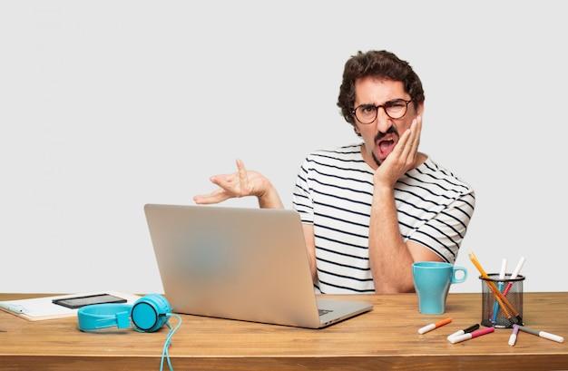 Junger bärtiger grafikdesigner mit einem laptop und einem verwirrten blick