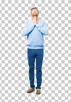 Junger blonder mann, der auf eine heilige art betet, bitten