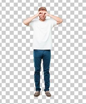 Junger blonder mann mit einem erschrockenen, erschrockenen ausdruck, augen mit beiden händen bedeckend und spähen.