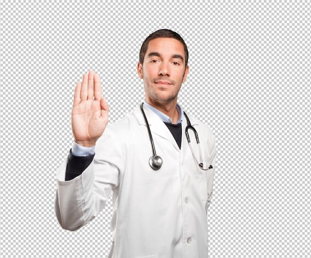 Junger doktor, der seine palme gegen weißen hintergrund zeigt