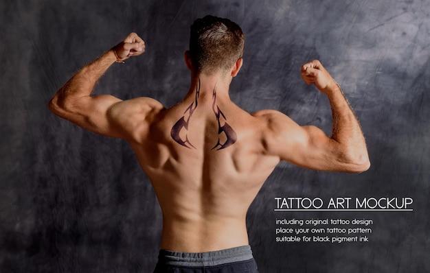 Junger fitness-mann, der tätowierung auf dem oberen rücken in einem dunklen fitnessstudio zeigt