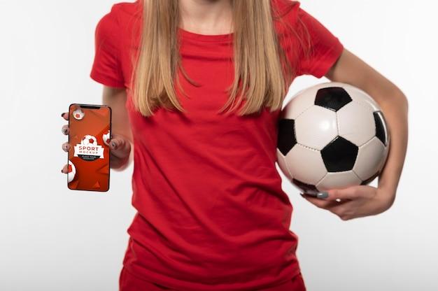 Junger fußballspieler, der ein digitales gerätemodell zeigt