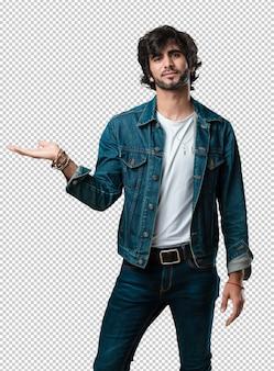 Junger gutaussehender mann, der etwas mit den händen hält, ein produkt zeigt, und fröhlich lächelt und einen eingebildeten gegenstand anbietet