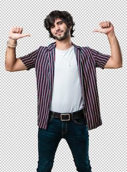 Junger gutaussehender mann stolz und überzeugt, finger, beispiel zeigend, um zu folgen, konzept der zufriedenheit, der arroganz und der gesundheit
