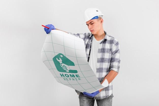 Junger handwerker, der auf einer blaupause schaut
