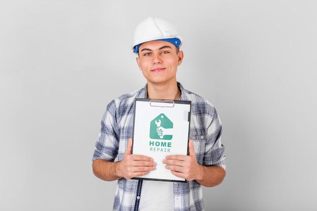 Junger handwerker, der eine modell-zwischenablage hält