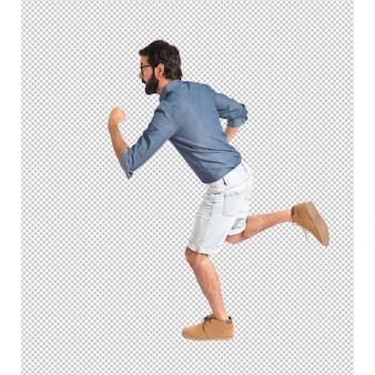Junger hippie-mann, der schnell über weißen hintergrund läuft