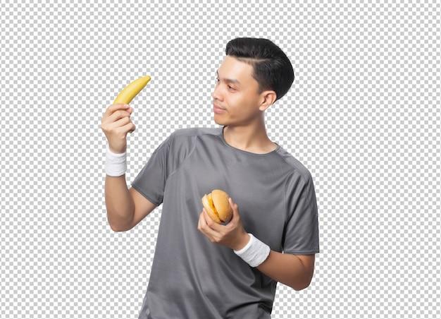 Junger hübscher asiatischer mann, der banane und hamburger hält