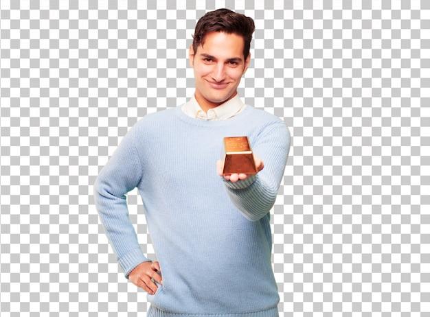 Junger hübscher gebräunter mann mit einem goldbarren