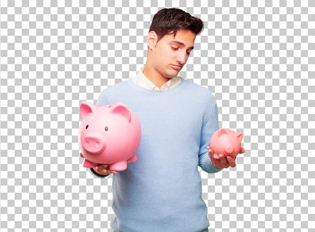 Junger hübscher gebräunter mann mit einem sparschwein