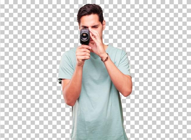 Junger hübscher gebräunter mann mit einer weinlesekino-kamera