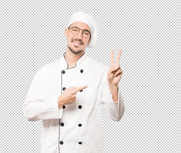 Junger koch, der eine geste nummer zwei macht