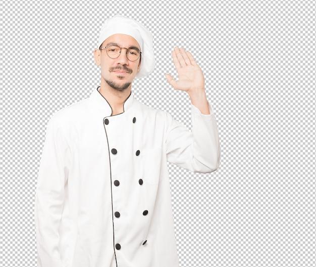 Junger koch winkt mit seiner hand