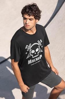 Junger männlicher skateboarder mit mock-up-t-shirt