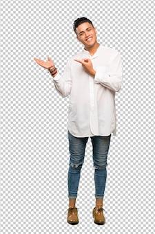 Junger mann, der copyspace eingebildet auf der palme hält, um eine anzeige einzufügen