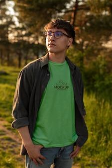 Junger mann, der draußen ein mock-up-t-shirt trägt