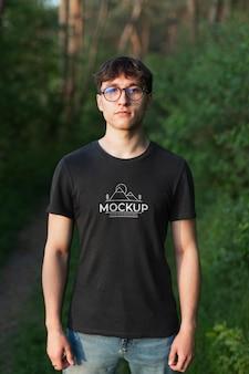 Junger mann, der ein modell-t-shirt im wald trägt