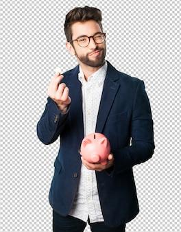 Junger mann, der ein sparschwein hält