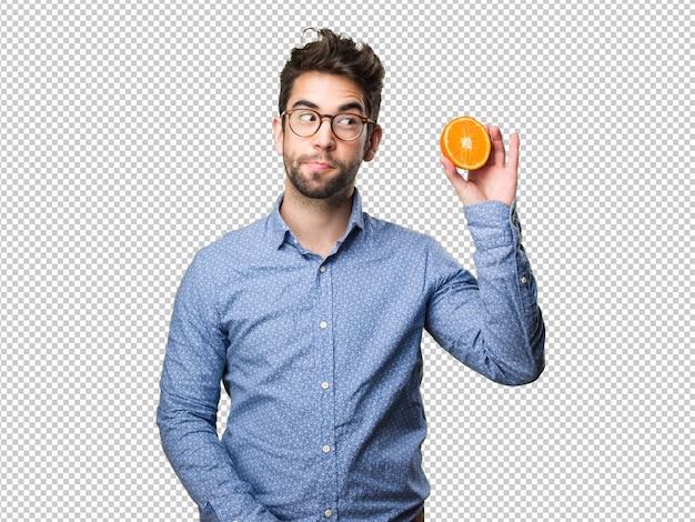 Junger mann, der eine orange anhält