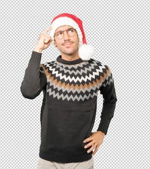 Junger mann, der eine weihnachtsmütze trägt, während isoliert gestikuliert