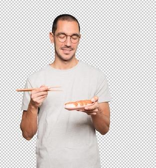 Junger mann, der essstäbchen verwendet, um sushi zu essen