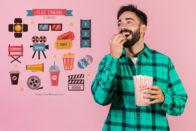 Junger mann, der popcorn nahe bei kinoelementen isst