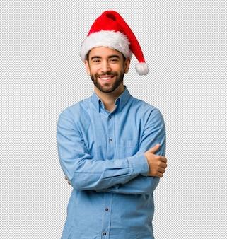 Junger mann, der sankt-hutüberfahrtarme trägt, lächelt und entspannt