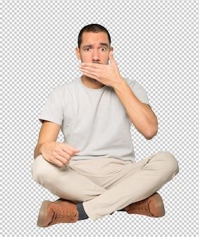 Junger mann, der seinen mund mit seinen händen bedeckt