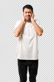 Junger mann mit dem weißen hemd, das beide ohren mit den händen bedeckt. frustrierter ausdruck