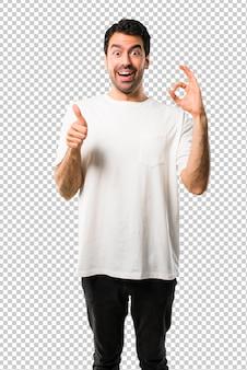 Junger mann mit dem weißen hemd, das ein okayzeichen mit den fingern zeigt und einen daumen herauf geste gibt
