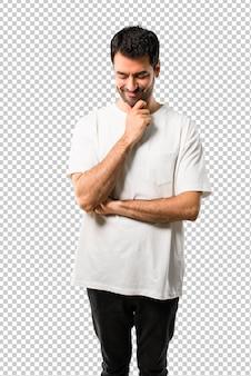 Junger mann mit dem weißen hemd, das unten mit der hand auf dem kinn steht und schaut